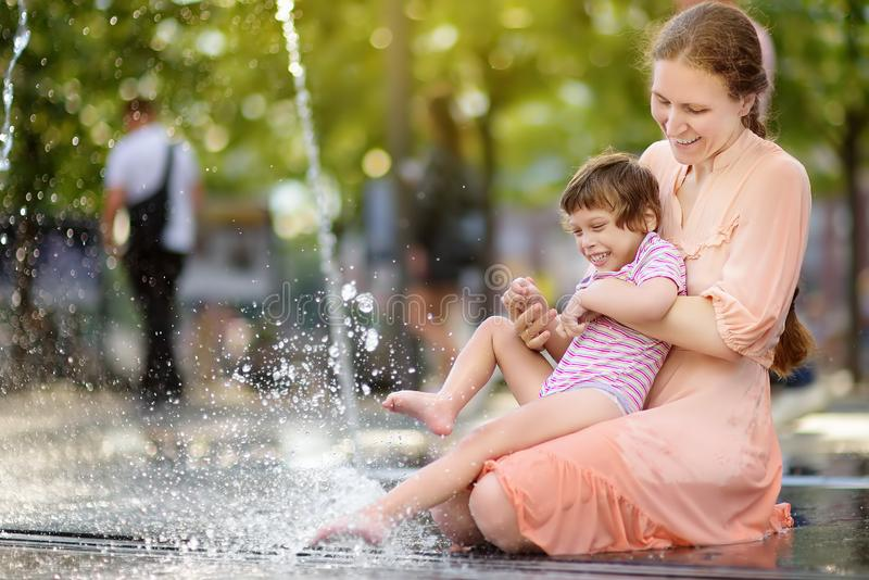 Retrato da menina deficiente bonita nos braços de sua mãe que tem o divertimento na fonte do parque público no dia de verão ensol foto de stock