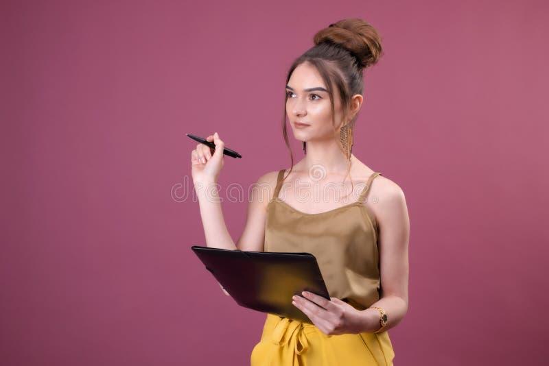 Retrato da menina do estudante com o dobrador da pena e do papel Escrita bonita nova do trabalhador algo em seus pap?is imagem de stock