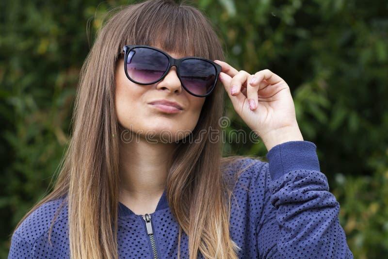 Retrato da menina do jovem adolescente nos óculos de sol no fundo das plantas verdes Menina à moda no parque fotografia de stock