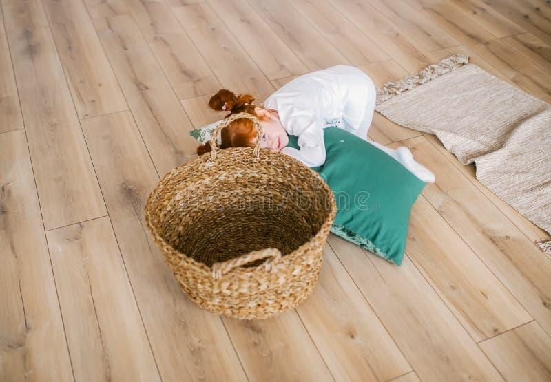 Retrato da menina do ruivo nos pijamas com a cesta do BIF no interior da casa fotos de stock royalty free