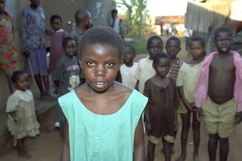 Retrato da menina do Ugandan com os amigos no fundo fotos de stock