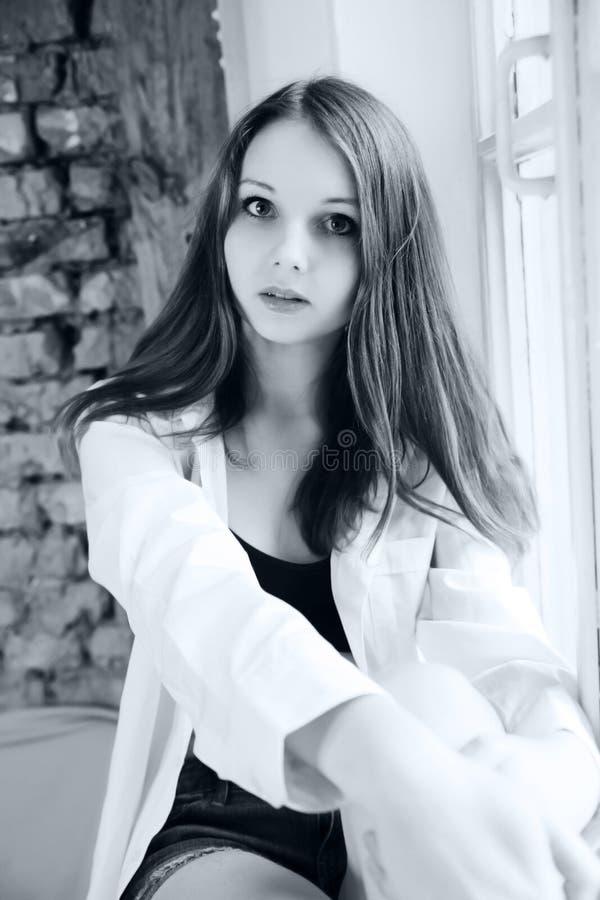 Retrato da menina encantador na camisa que senta-se na soleira preto fotos de stock