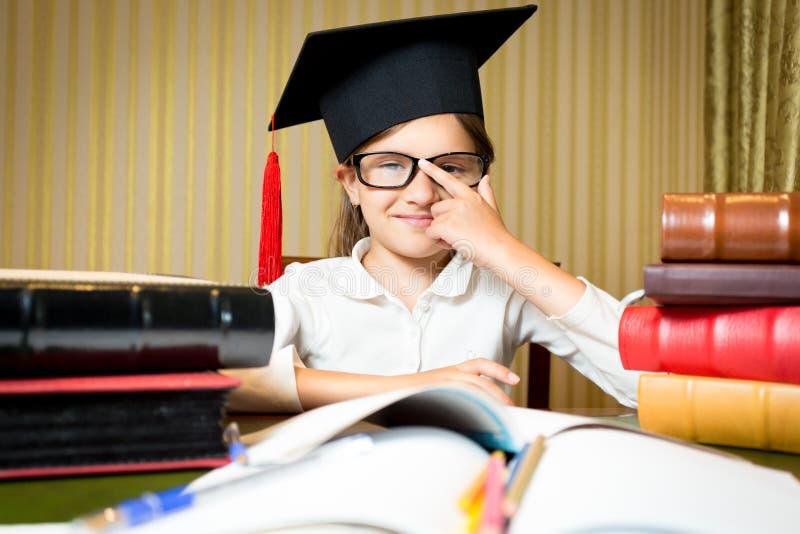 Retrato da menina esperta no tampão da graduação que guarda monóculos fotos de stock