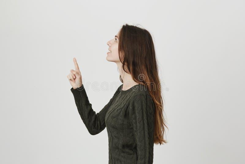 Retrato da menina europeia magro atrativa nova, apontando o indicador e olhando acima com sorriso bonito sobre o branco fotos de stock