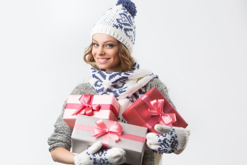 Retrato da menina feliz bonita no chapéu e nos mitenes da camiseta com as caixas de presentes do Natal fotografia de stock royalty free