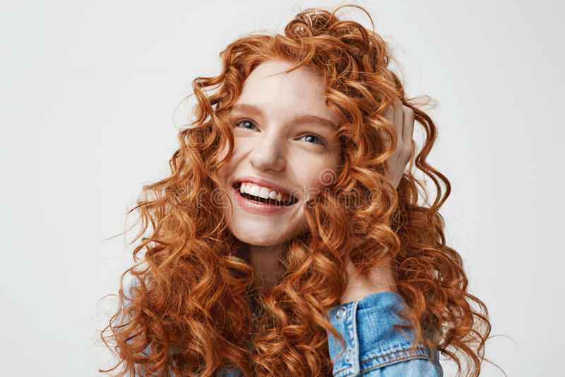 Retrato da menina feliz bonito que sorri tocando em seu cabelo vermelho encaracolado sobre o fundo branco imagem de stock royalty free
