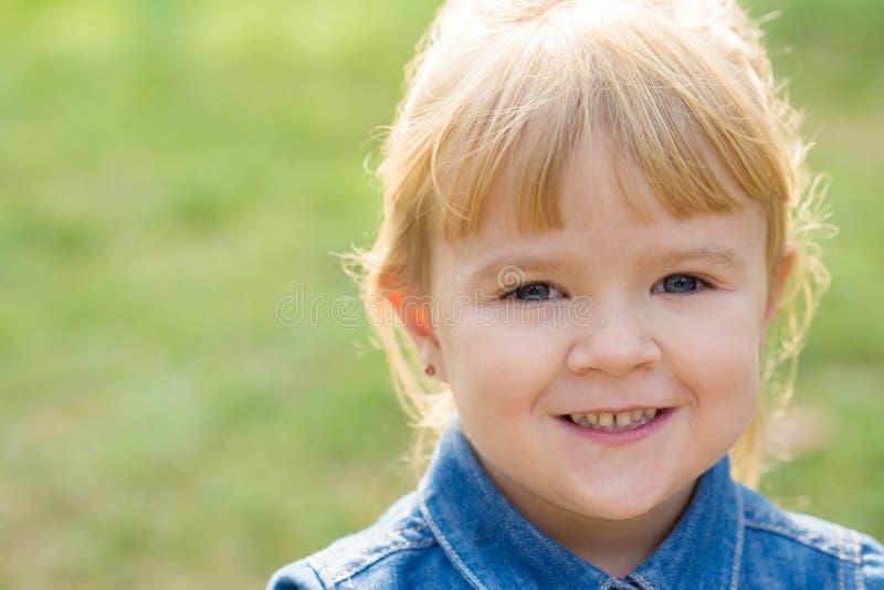 Retrato da menina feliz com sorriso na cara no dia ensolarado foto de stock