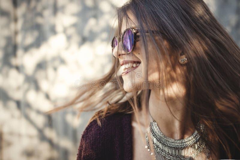 Retrato da menina feliz do boho no equipamento e em óculos de sol frescos que sorri na rua ensolarada Menina despreocupada do mod fotos de stock
