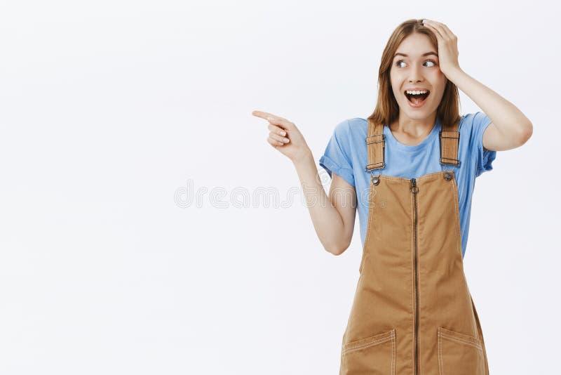 Retrato da menina feliz e surpreendida entusiasmado que encontra de repente a mão popular da terra arrendada da pessoa na cabeça  imagem de stock royalty free
