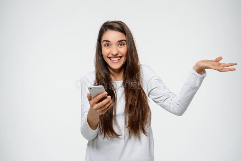 Retrato da menina feliz nova que guarda sua ondulação disponivel do telefone sobre o fundo branco fotos de stock royalty free
