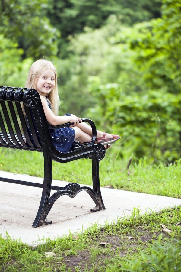 Retrato da menina feliz que senta-se no banco no parque imagem de stock royalty free