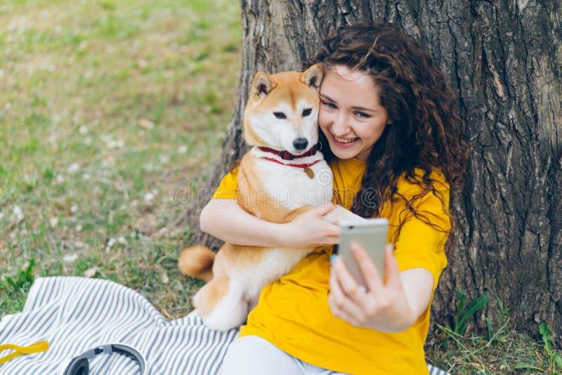 Retrato da menina feliz que toma o selfie com o cão no parque que abraça a câmera da terra arrendada do animal de estimação imagem de stock royalty free