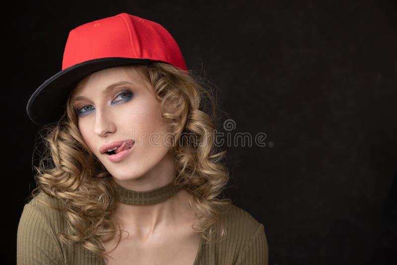 Retrato da menina impertinente no tampão vermelho fotos de stock royalty free