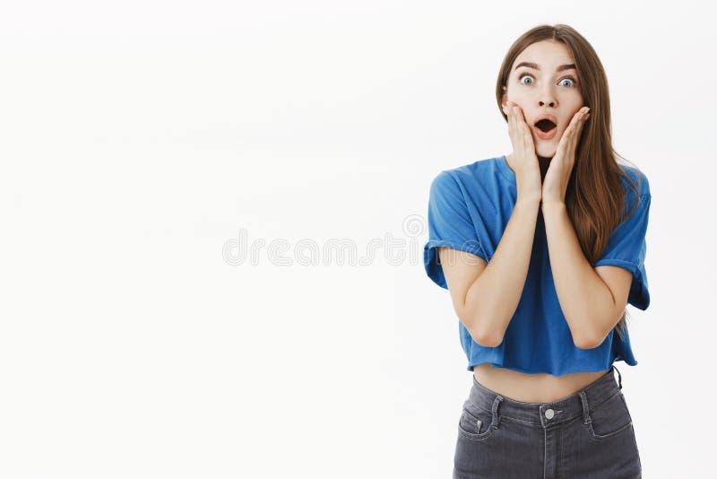 Retrato da menina impressa e surpreendida da bisbolhetice com cabelo marrom na maxila deixando cair de ofego do t-shirt azul da p imagens de stock royalty free