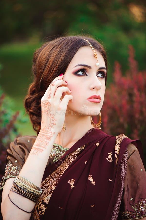 Retrato da menina indiana bonita Modelo hindu novo da mulher com mehndi do tatoo e joia kundan Indiano tradicional foto de stock
