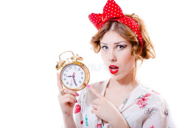 Retrato da menina loura bonita do pinup que mostra em 9 30 no despertador & vista da câmera surpreendida no fundo branco imagem de stock royalty free