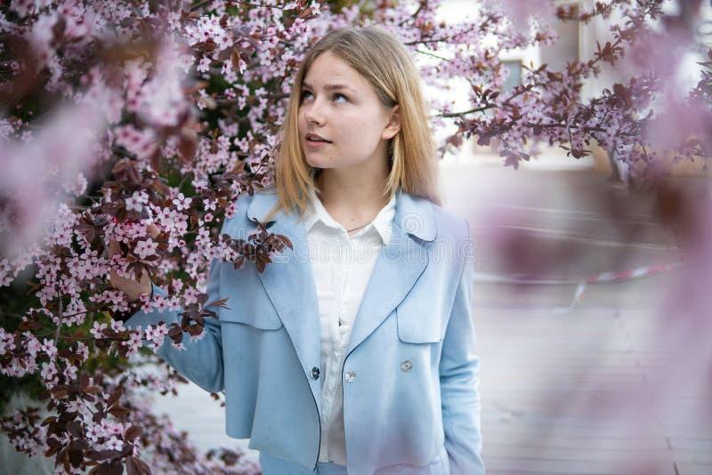 Retrato da menina loura bonita que levanta em ramos de árvore de florescência com flores cor-de-rosa Esta??o de mola foto de stock
