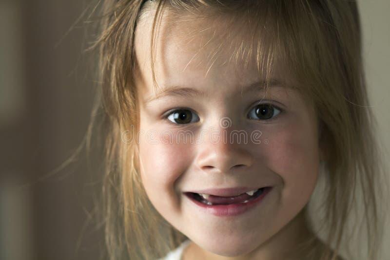 Retrato da menina loura bonito pequena da jovem criança com olhos cinzentos que sorri in camera com sorriso desdentado engraçado  imagens de stock