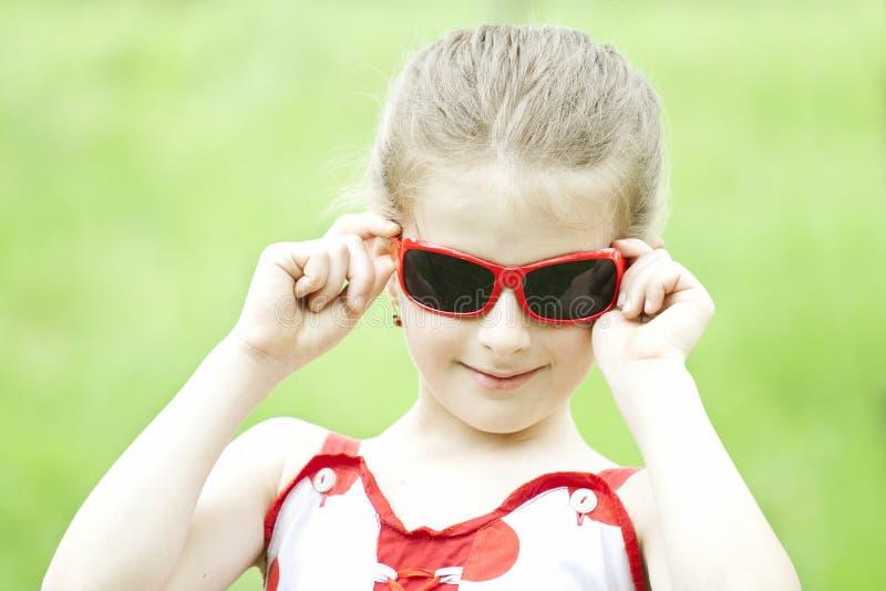 Retrato da menina loura com óculos de sol vermelhos imagens de stock royalty free