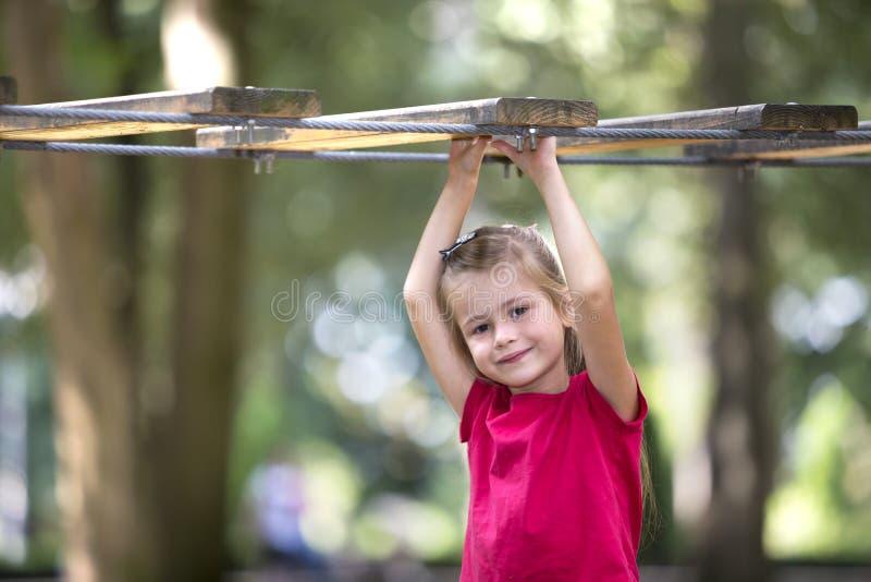 Retrato da menina loura de sorriso adorável bonito da criança no vestido cor-de-rosa do verão com terra arrendada de braços levan fotos de stock