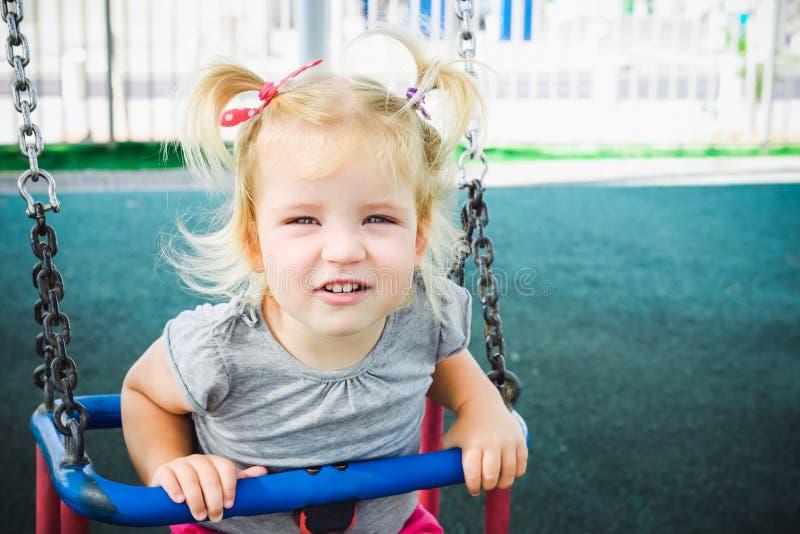 Retrato da menina loura emocional da criança pequena que olha a câmera e que tem o divertimento em um balanço exterior Campo de j fotografia de stock royalty free