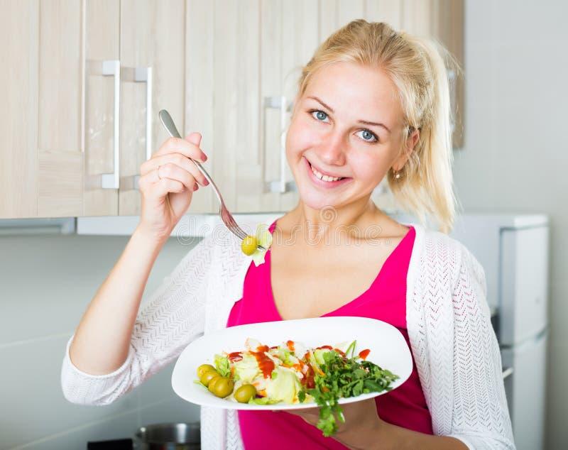 Retrato da menina loura feliz que come a salada imagens de stock