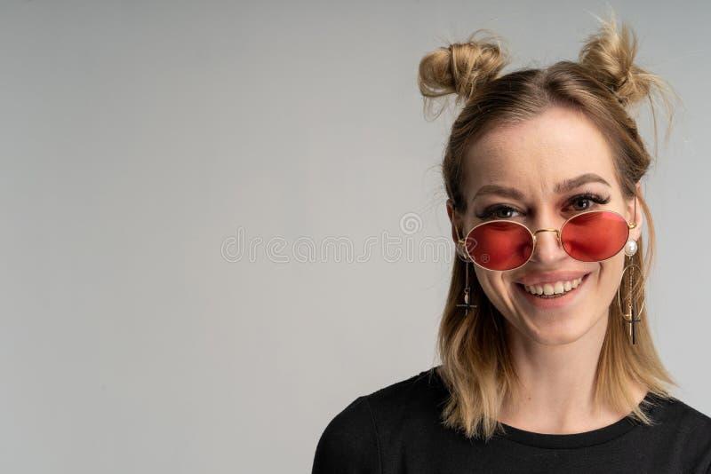 Retrato da menina loura nova bonita no vestido preto e em óculos de sol redondos foto de stock