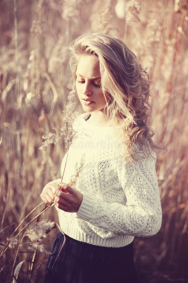 Retrato da menina loura nova bonita pensativa em um campo no pulôver branco, no conceito da saúde e na beleza fotos de stock royalty free