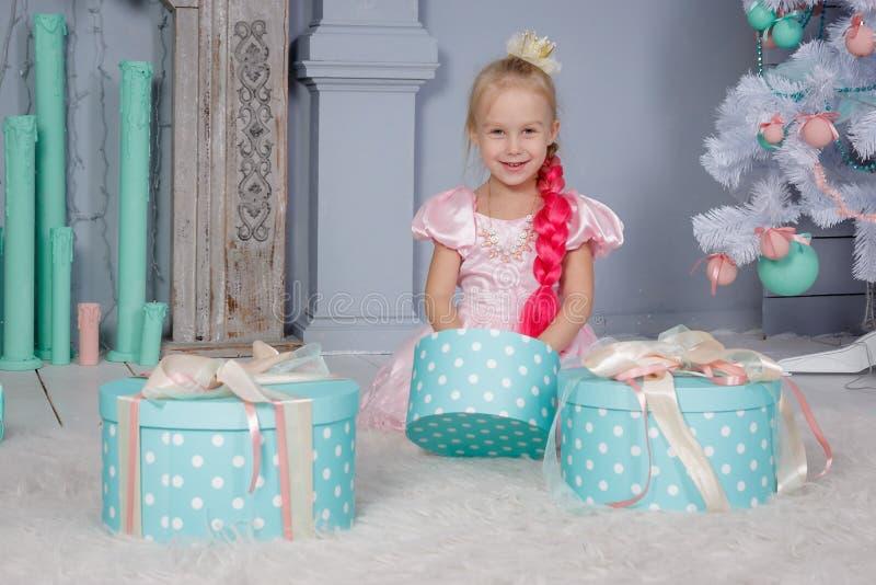 Retrato da menina loura pequena europeia bonito da princesa com a coroa no vestido bonito que senta-se no assoalho e nos presente imagens de stock