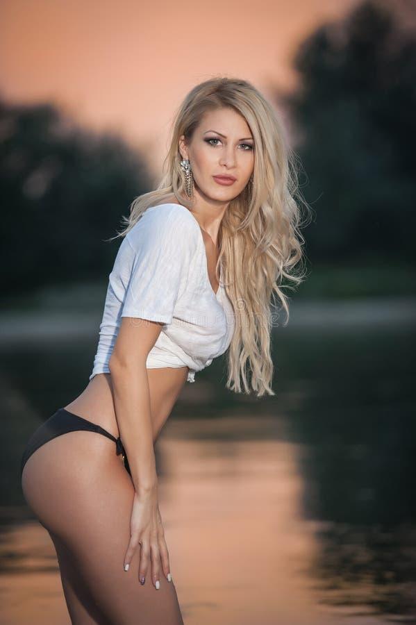 Retrato da menina loura 'sexy' nova no biquini que levanta provocatively na praia no por do sol Mulher atrativa sensual na cuecas imagem de stock