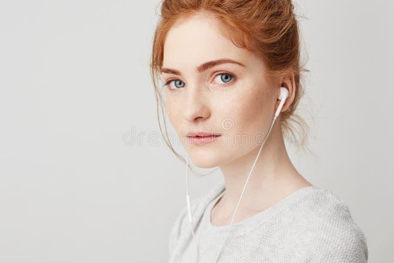 Retrato da menina macia bonita nova do ruivo com olhos azuis nos fones de ouvido que olham a câmera que sorri sobre o branco imagens de stock