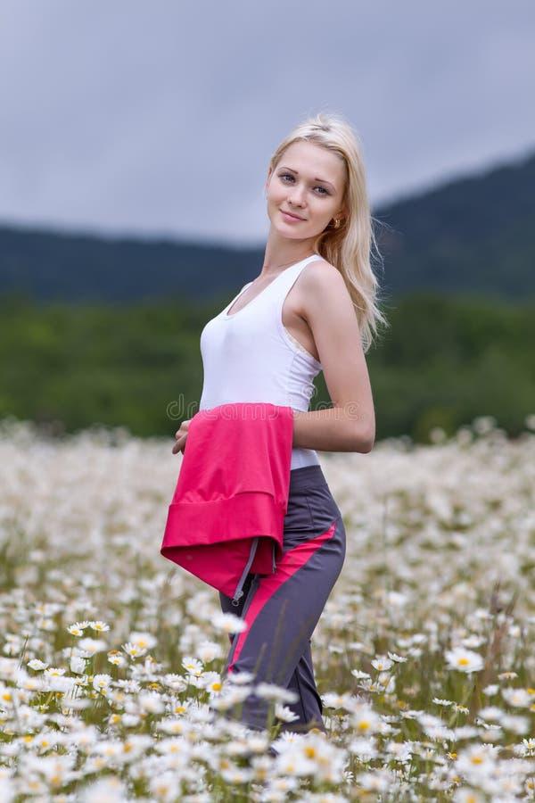 Retrato da menina magro no sportswear no campo da camomila foto de stock