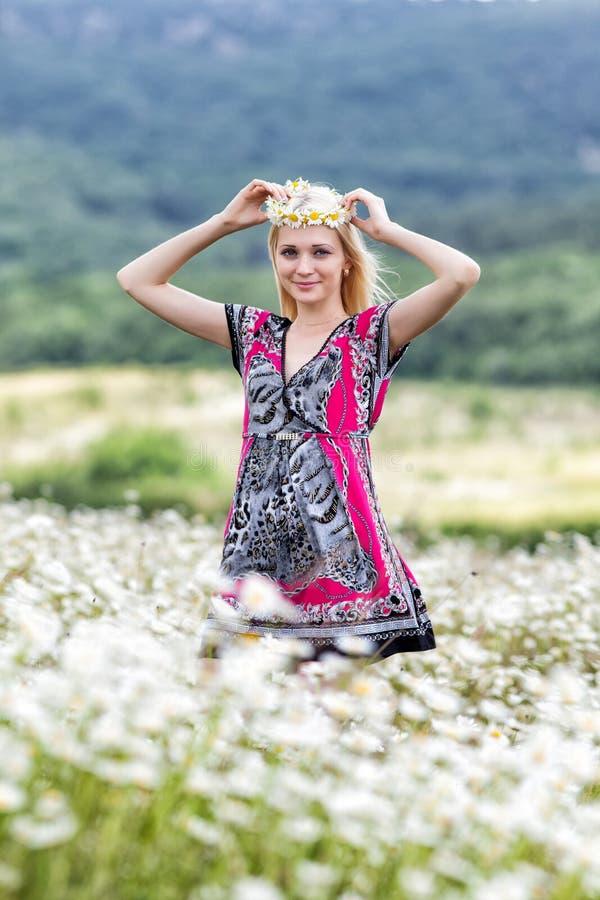 Retrato da menina magro no vestido leve no campo da camomila imagem de stock