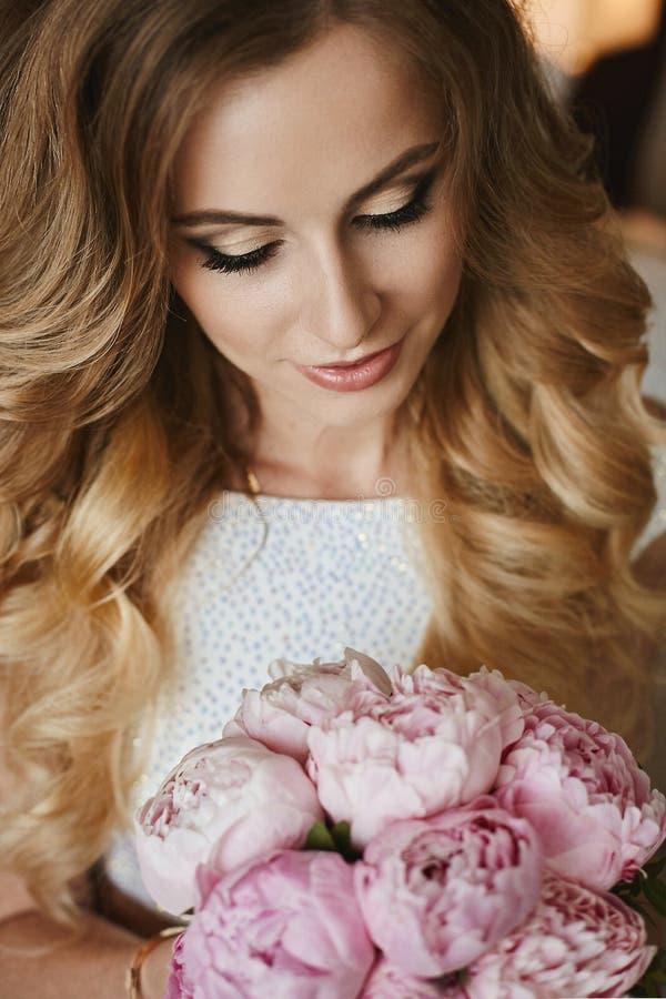 Retrato da menina modelo loura elegante e bonita com composição brilhante e com cabelo encaracolado, em um vestido brilhante à mo imagem de stock
