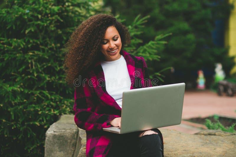 Retrato da menina moreno agradável do cabelo encaracolado com o portátil que senta-se em um banco fora imagens de stock