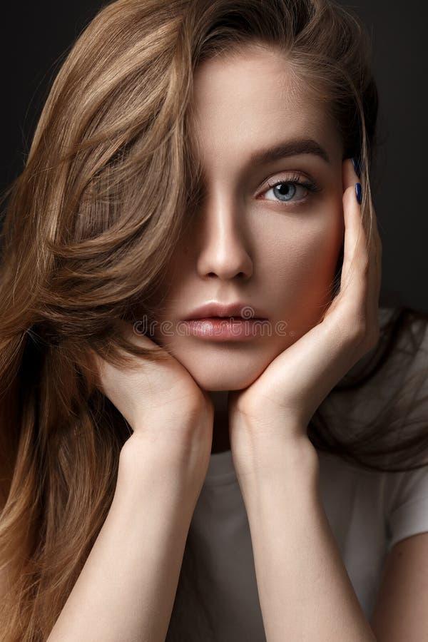 Retrato da menina moreno bonita com o cabelo de fluxo longo vestido no t-shirt branco no fundo escuro no estúdio fotos de stock royalty free