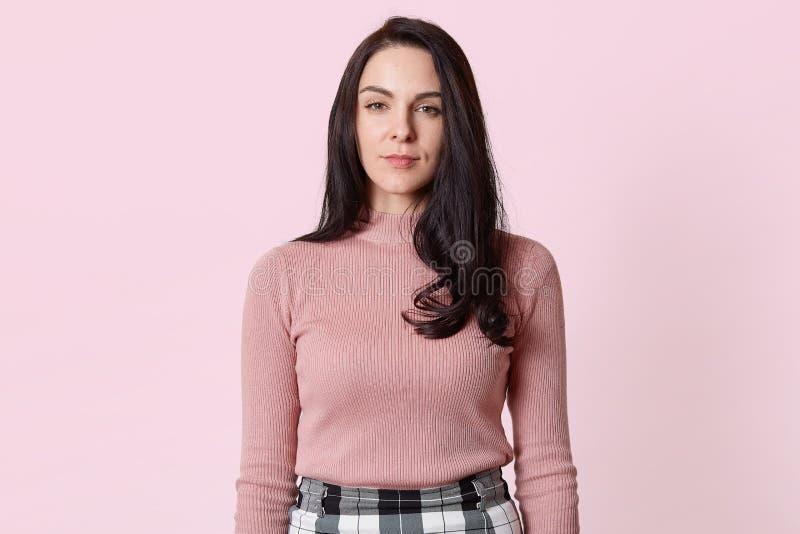 Retrato da menina moreno nova com cabelo escuro longo e a pele saudável que vestem a camisa cor-de-rosa e a saia quadriculado, ol fotos de stock