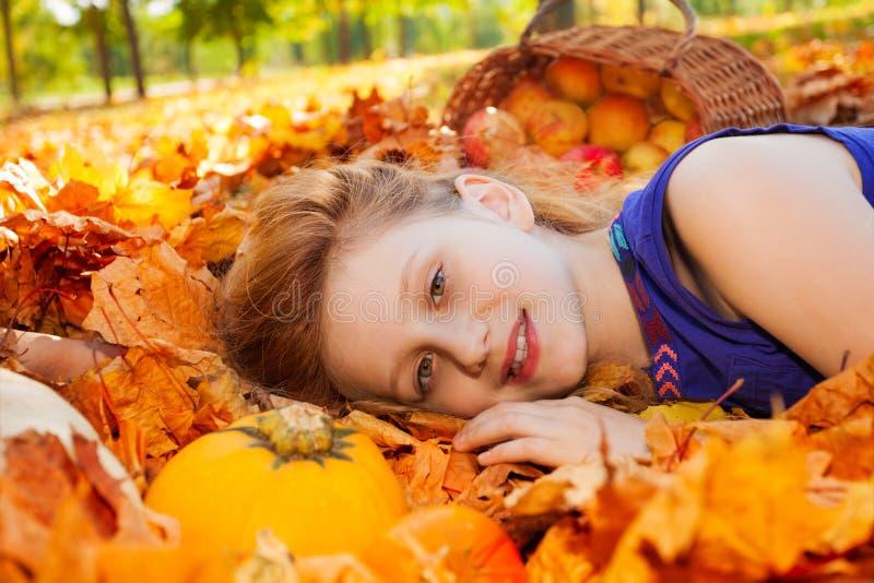 Retrato da menina nas folhas com abóbora e maçãs imagens de stock