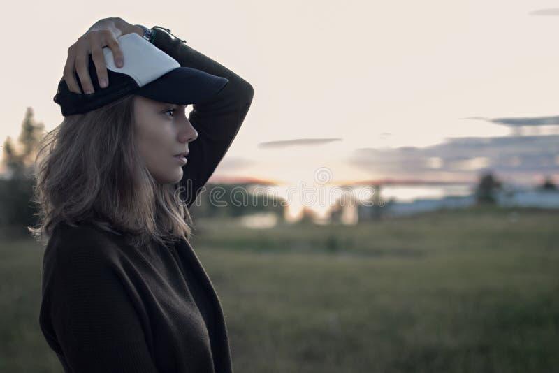 Retrato da menina no chapéu no perfil no por do sol e dos campos com tal foto de stock royalty free