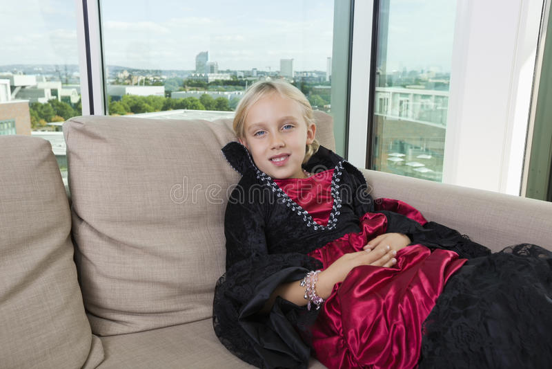 Retrato da menina no traje do vampiro que relaxa no sofá em casa fotografia de stock