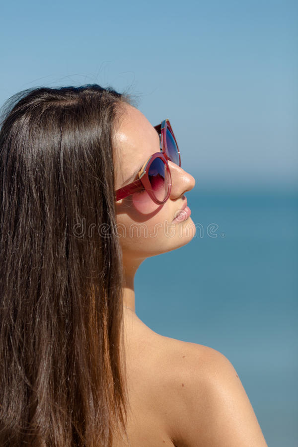 Retrato da menina nos óculos de sol no fundo do mar fotos de stock royalty free