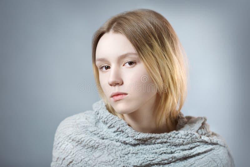 Retrato da menina pensativa em cores pastel cinzentas foto de stock