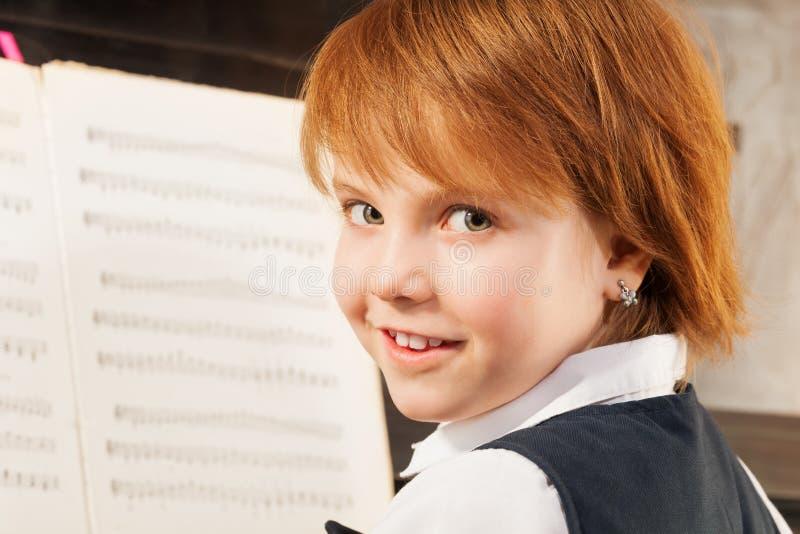Retrato da menina pequena bonita que joga o piano fotografia de stock