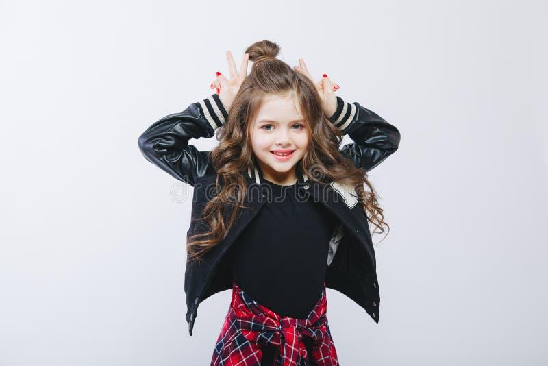 Retrato da menina pequena do moderno no revestimento de bombardeiro que mostra chifres pelas mãos posing Penteado moderno encarac foto de stock
