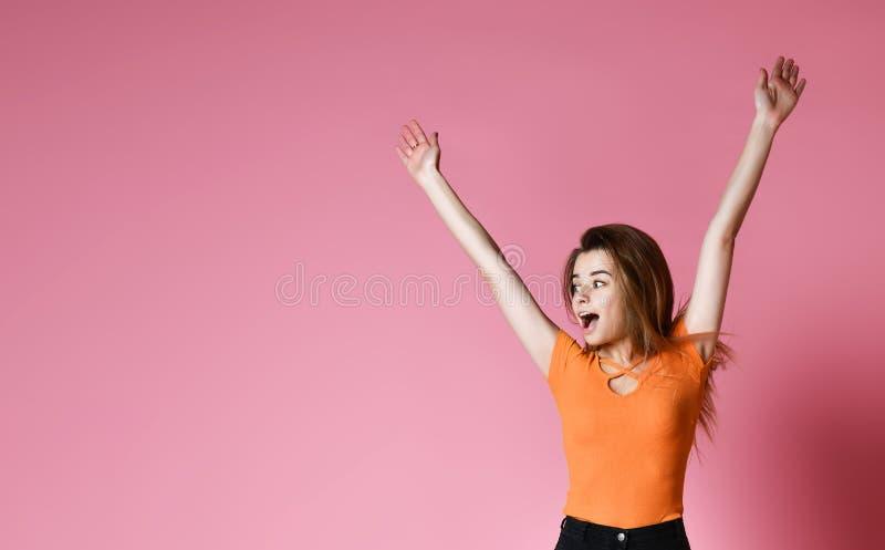 Retrato da menina positiva alegre que salta no ar que olha afastado a câmera isolada no fundo cor-de-rosa foto de stock