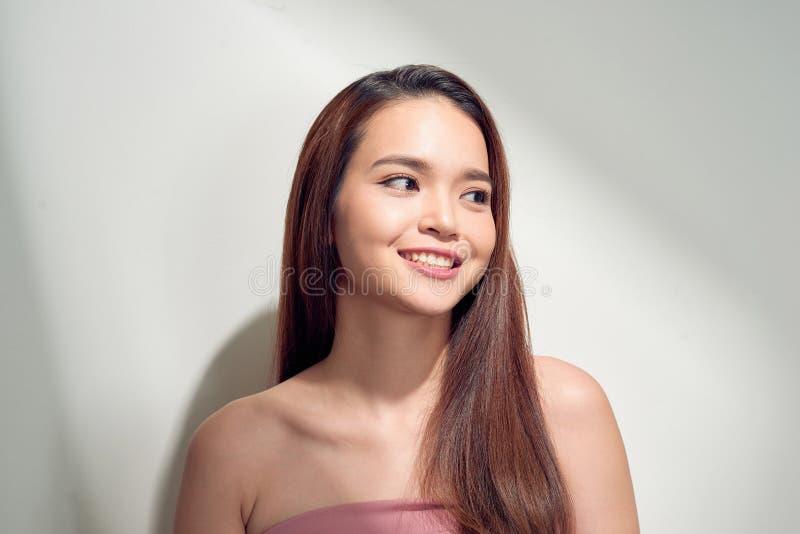 Retrato da menina positiva com sorriso branco de irradia??o que aprecia a luz do sol que olha afastado tendo no fundo branco imagens de stock