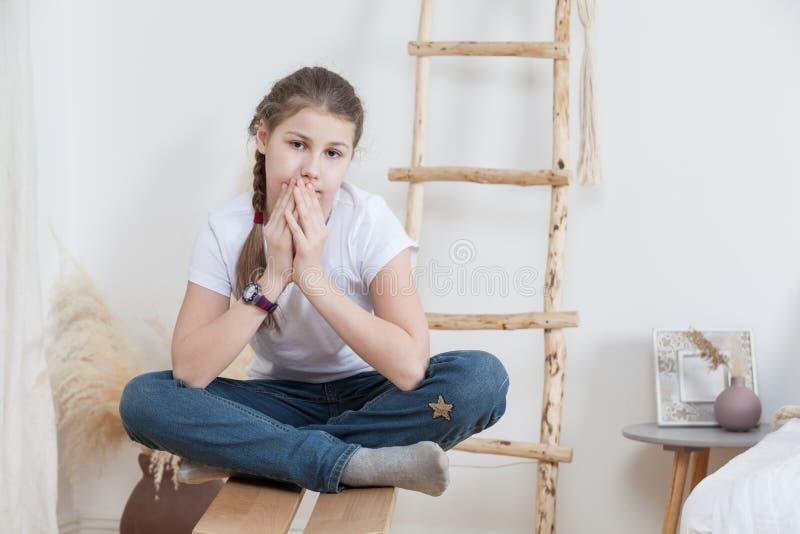Retrato da menina pre adolescente calma que veste a calças de ganga e o t-shirt branco, sentando-se no banco em sua sala foto de stock royalty free