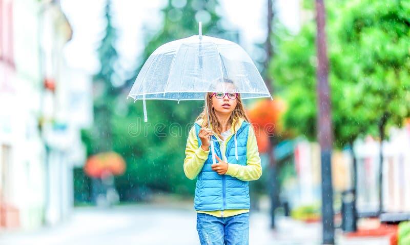 Retrato da menina pre-adolescente nova bonita com o guarda-chuva sob a chuva imagem de stock royalty free