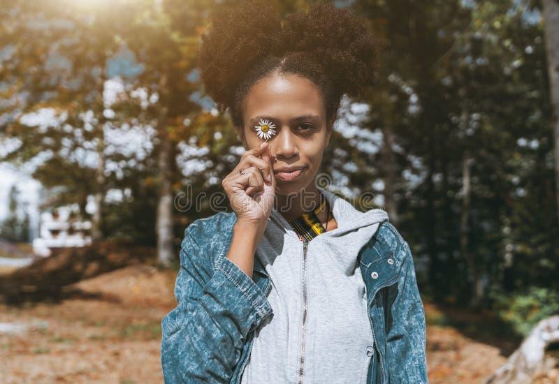 Retrato da menina preta que esconde seu olho com a camomila imagens de stock