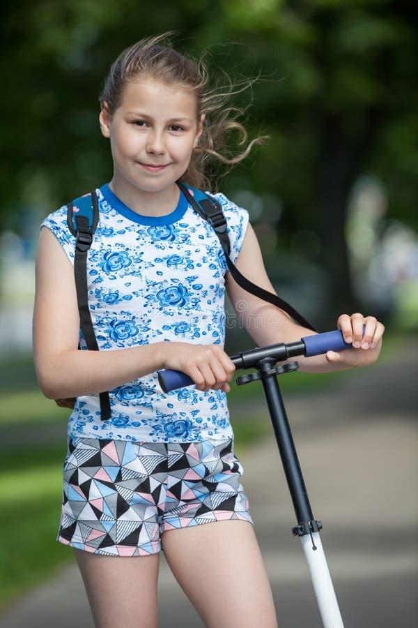 Retrato da menina preteen caucasiano com a roda do 'trotinette' do pontapé nas mãos, exterior imagem de stock